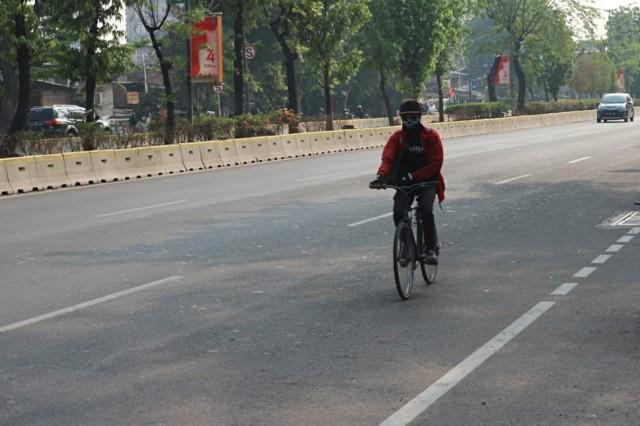Pengendara sepeda berkendara di luar jalur sepeda