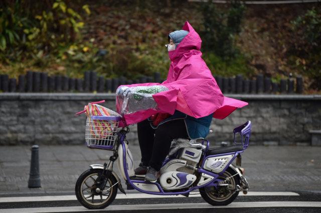 Virus corona, wuhan wanita dengan skuter