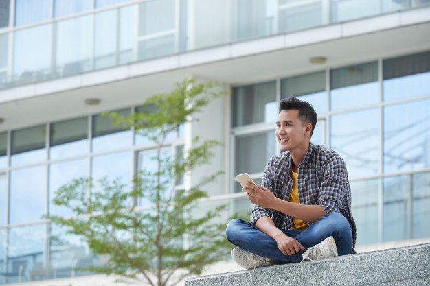 asian-student-sitting-campus-stairs-outdoors-with-smartphone-staring-distance_1098-19282.jpg