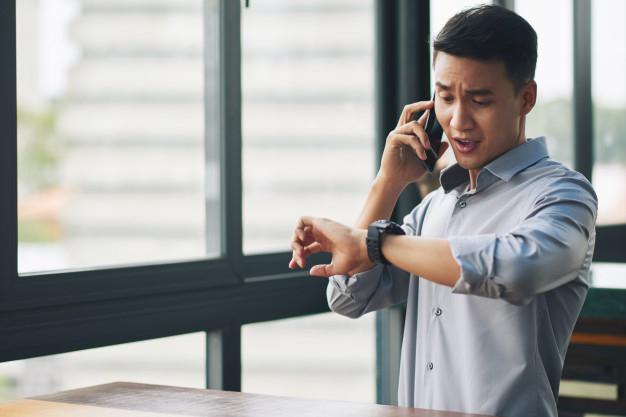 panicking-asian-man-talking-mobile-phone-looking-wristwatch_1098-17413.jpg