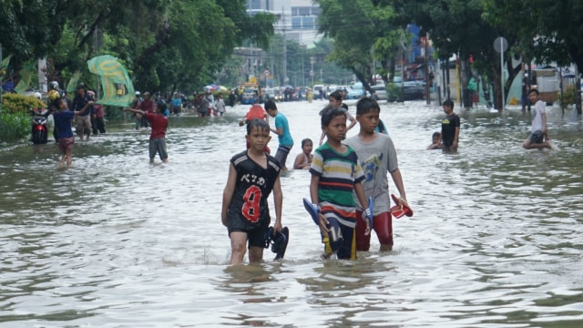 Anak-anak bermain saat Banjir Jakarta