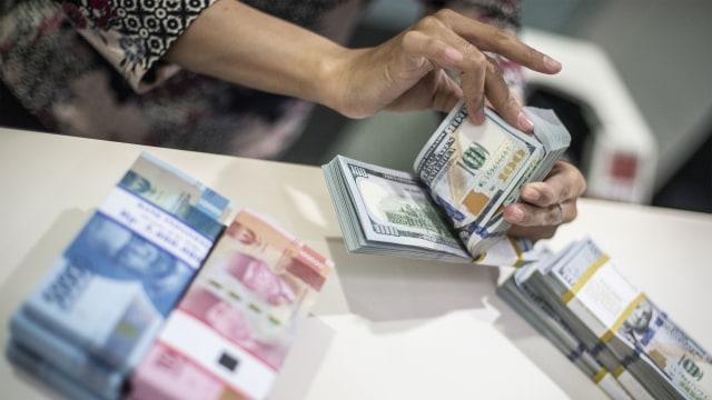 Karyawan menghitung uang dolar AS