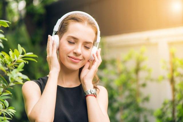 woman-wearing-black-sleeveless-dress-holding-white-headphone-1001850.jpg