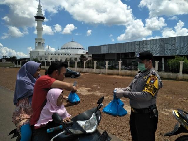 Polisi dan Warga Tionghoa di Batam Bagikan Masker dan Nasi Kotak ke Pengendara (60182)