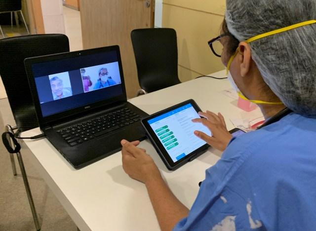 Dokter di India memeriksa pasien secara online.