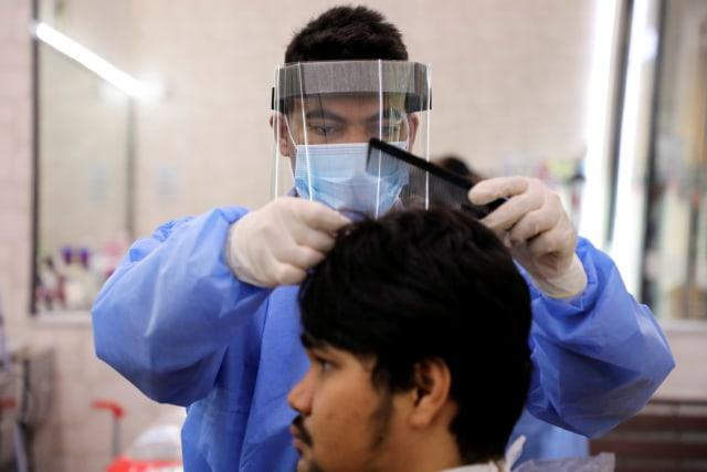 Foto: Tukang Pangkas Rambut di Kuala Lumpur Gunakan APD  (809737)