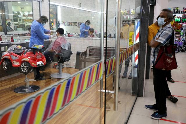 Foto: Tukang Pangkas Rambut di Kuala Lumpur Gunakan APD  (809740)