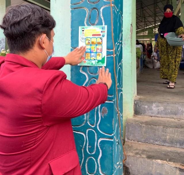 PMM UMM Lakukan Penempelan Poster Adapatasi Kebiasaan Baru di Pasar Benuo (405468)
