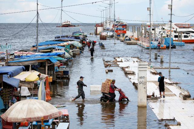 Foto: Aktivitas Warga di Tengah Genangan Banjir Rob di Pelabuhan Kali Adem (590496)