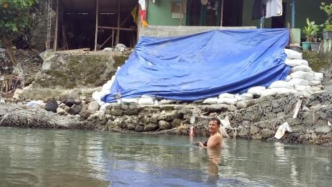 Suyono di depan talud sungai yang roboh.