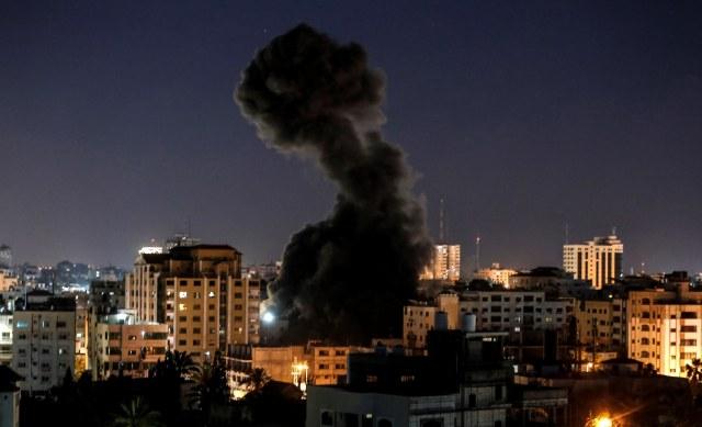 Asap mengepul di atas bangunan selama serangan udara Israel di Kota Gaza, Palestina. Foto: AFP/Mahmud Hams
